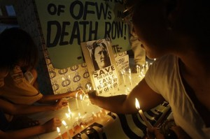 Activists and supporters place candles near slogans during an overnight vigil at a chapel in suburban Quezon City, north of Manila, Philippines on Tuesday March 29, 2011, near the home of one of three Filipinos that are set to be executed in China. The group called for the government to help save the lives of three Overseas Filipino Workers (OFWs) who are set to be executed March 30, after being sentenced by Chinese authorities for drug trafficking. China is set to execute the three Filipinos despite appeals for clemency by the Philippine Government, officials said. (AP Photo/Aaron Favila)