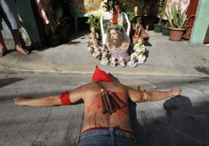 A hooded penitent with a bloodied back prays while lying on his belly in front of an image of Jesus Christ during Maundy Thursday Lenten rites in Mandaluyong city, metro Manila March 28, 2013. Maundy Thursday or Holy Thursday is the day Christians commemorate the Last Supper of Jesus Christ. Holy Week is celebrated in many Christian traditions during the week before Easter. (MNS photo)