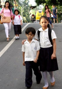 A senior elementary student guides her little brother for a long walk to reach their school at Barangay North Fairview Elementary School in Quezon City Monday (June 3,2013). (MNS photo)