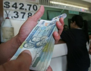A man arranges his peso bills inside a currency exchange shop Friday, Nov. 9, 2007, in Manila, Philippines. The dollar closed Friday at 42.795 pesos, where the peso rose to a new seven-year high on prospects of further U.S. interest rate cuts and likely increases in remittances from Filipinos overseas.  (AP Photo/Pat Roque)