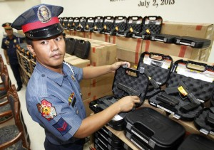 member of the Philippine National Police (PNP) shows the new Glock 17 Generation 4 pistols after a distribution ceremony of the pistols at the police headquarters in Manila July 2, 2013. Philippine President Benigno Aquino attended the ceremony in which 22,603 pistols were distributed to PNP officers as part of the government's effort to arm each police officer in the country with a handgun in order to strengthen the police force, local media reported. (MNS photo)