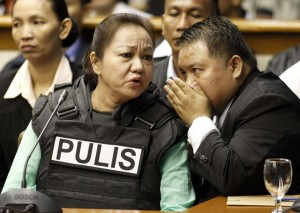 Janet Lim Napoles, wearing a bullet proof vest, listens as her lawyer Howard Areza whispers to her while Napoles attended a public inquiry at the Senate in Manila that was held last year. Latest reports said she implicated more lawmakers and officials as apparently involved in the scam.