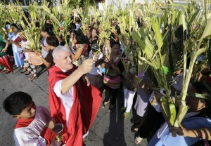 Filipinos raise palm fronds to receive a blessing from Italian priest Romulo Bertoni (2nd from left) to mark Palm Sunday at a shopping mall parking area in Las Pinas City, south of Manila, the Philippines, 13 April 2014. Palm Sunday for Roman Catholic devotees symbolically marks the biblical account of the entry of Jesus Christ into Jerusalem, signaling the start of the Holy Week. (MNS photo)