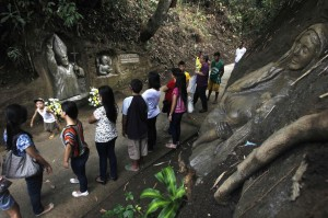 Visitors look at an image of Pope John Paul II carved opposite an image of the Virgin Mary (R) on a hillside in Maragundon town, Cavite city, south of Manila April 26, 2014. Sculptors Val and his brother Oca Suarez, finished sculpting of image of Pope John Paul II in two days. . Pope John XXIII, who reigned from 1958 to 1963 and called the modernizing Second Vatican Council, and Pope John Paul II, who reigned for nearly 27 years before his death in 2005 and whose trips around the world made him the most visible pope in history, will be declared saints by Pope Francis at an unprecedented twin canonization on Sunday.  (MNS photo)