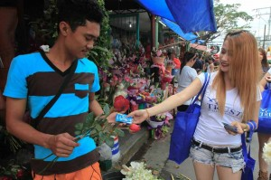 A man receives a pack of condoms from a saleslady, as part of a promotional gimmick, on the eve of Valentine's Day in Manila on Friday. Despite the Catholic church teachings against contraceptives, motels in Manila are packed with couples spending Valentine's Day. (MNS photo)