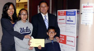 Cerritos Mayor Mark Pulido and his wife Gloria pose with their children for a photo after they cast their votes on March 3.