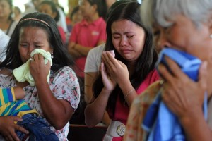 Relatives of footwear factory workers weep during a special Mass in Manila on Monday for the 72 people who were killed during the fire. Authorities are still investigating if conditions in the factory contributed to the death of the workers. Many of those who died were workers trapped during the blaze. (MNS photo)