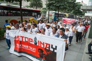 Veteran singer Jim Parades (4th left in front) leads other protesters as they march around the financial district of Makati on Wednesday to stop Vice President Jejomar Binay from running for the presidency. The group cites allegations of corruption against Binay makes him unfit for the job. (MNS Photo)