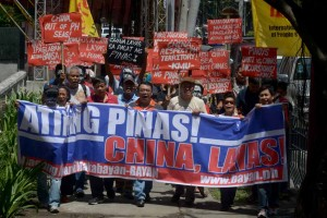 Protesters rally in front of the Chinese Consulate in Makati City on Tuesday, denouncing China's claim to most of the West Philippine Sea including areas claimed by the Philippines. The protest comes as a UN tribunal in the Hague begins a hearing the Philippines' claim on the disputed Spratly Islands.(MNS photo)