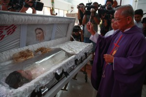 A priest douses holy water on the remains of Jennifer Laude. The suspect in her death, as US Marine, has been charged with murder. (MNS photo)