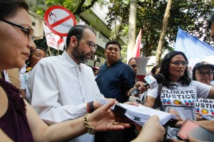 Commission on Human Rights Chairperson Chito Gascon receives a complaint from typhoon victims and climate justice advocates in Quezon City, Tuesday. The complaint seeks an investigation into 50 investor-owned fossil fuel companies for their accountability for climate impacts.  (MNS photo)