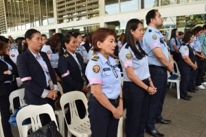 "Airport security screeners wear pink armbands during a Mass at the Ninoy Aquino International Airport on Friday. The security screeners appeal for public understanding while investigation of the ""tanim-bala"" scam is underway. (MNS photo)"