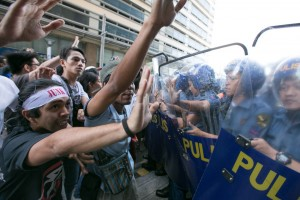 Activists from the League of Filipino Students try to break through the police barricade during a protest action across the US Embassy in Manila on Tuesday. The group slammed the economic policies under the Asia Pacific Economic Cooperation, which allegedly perpetuates the commercialization of education in the country.(MNS photo)