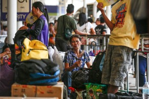 Commuters wait for their bus rides at the Cubao bus terminal on Friday. Authorities have beefed up security around the country as thousands are expected to travel to the provinces in observance of All Saints' Day and All Souls' Day this weekend.(MNS photo)