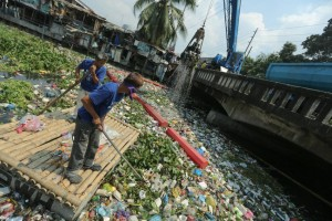 Maintenance workers clear debris from a river as a crane scoops up garbage from the Estero de San Miguel in Manila on Monday. The clean-up drive was implemented since Saturday to address water pollution and prevent the spread of water-borne diseases.(MNS photo)
