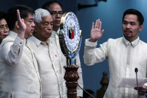 """Neophyte Senator Emmanuel Pacquiao (right) administers the oath of office of newly-elected Senate President Aquilino Pimentel III during the opening of the Senate session under the 17th Congress on Monday (July 25, 2016) at the Plenary Hall of the Senate Building in Pasay City. Also in photo are immediate members of the Pimentel family, including former Senate President Aquilino """"Nene"""" Pimentel Jr. (center). (MNS photo)"""