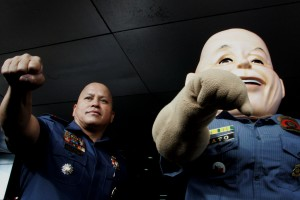"""Police Director General Ronald M. Dela Rosa, together with """"PO1 Bato"""", a mascot depicting the PNP chief, show their fists, which symbolizes their fight against illegal drugs, during the 24th Police Community Relations Group Founding Anniversary on Monday (August 1, 2016) at National Headquarter Philippine National Police (NHQ, PNP), Camp Crame in Quezon City.  (MNS photo)"""
