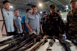 President Rodrigo R. Duterte glances at the firearms recovered from the New People's Army (NPA) rebels during his visit at Camp Edilberto Evangelista in Patag, Cagayan de Oro City on August 9. (MNS photo)