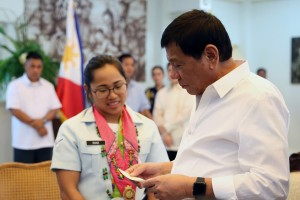 President Rodrigo Duterte looks at the check worth P5-million before handing it over to Hidilyn Diaz, the first Filipina and Mindanaoan Olympic silver medalist, during a courtesy call at the Presidential Guest House in Panacan, Davao City on August 11. (MNS photo)