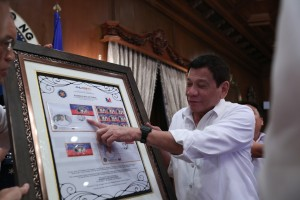 President Rodrigo Duterte receives commemorative stamps featuring his presidential inauguration after the 5th Cabinet meeting in Malacañan's State Dining Room on August 22. (MNS photo)