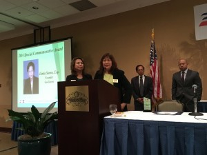 """Honoring Linda Sarno, Esq – The husband of the late Linda Sarno, Engr. Phil Sarno and his son, Mike Sarno,  listen as Faccoc Director Gloria Rull memorializes the person responsible for the Fil Am Chambers joining the advocacy on """"going green"""". With her near the podium is Director Edith Andres."""